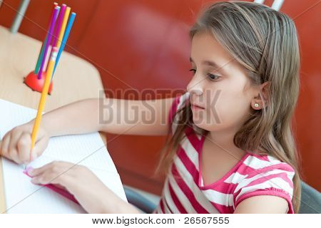 Lovely girl working on her school project at home