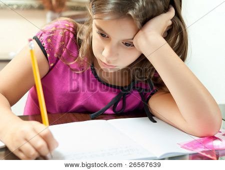 Small girl looking bored while working on her school project at home