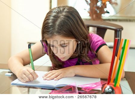 Beautiful girl working on her school project at home