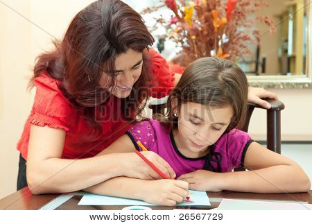 Young latin mother helping her daughter with her school homework