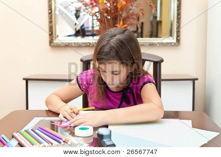 Beautiful small hispanic girl working on her art project at home