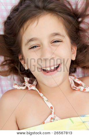 Beautiful little hispanic girl laughing in her bed with a pink plaid sheets background
