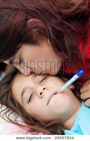 Madre Latina besando a su hija enferma que tiene un termómetro en la boca