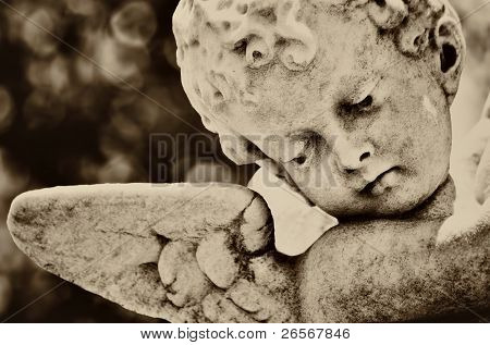 Old statue of an infant angel with a diffused background in sepia shades