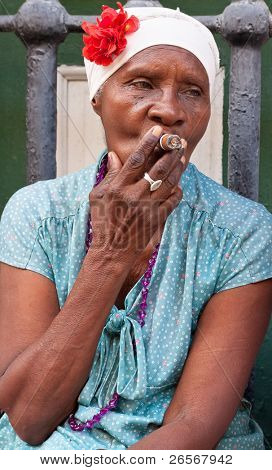 HAVANA-MAY 19:Lady smoking a huge cigar May 19,2011 in Havana.Iconic characters like this are an attraction for the more than 2 million tourists who go to Cuba each year to enjoy its distinct culture