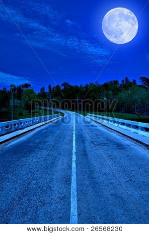Lonely road surrounded by the forest illuminated by a bright full moon at midnight