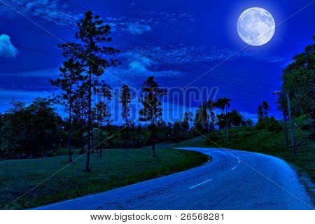Lonely road in the country illuminated by a bright full moon at midnight