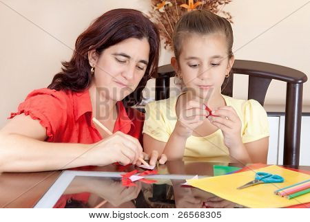Latin mother and daughter working on an art project at home with some art supplies on the table