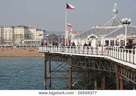 BRIGHTON,UK-MARCH 31:Visitors at the pier March 31,2011 in Brighton.Finished in 1899 and occupied by restaurants,arcades and fair rides the pier is a grade II listed building and an icon of the city