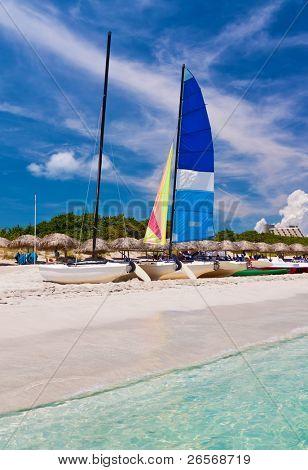 Catamaran, water bikes and thatched umbrellas in the beautiful beach of Varadero in Cuba
