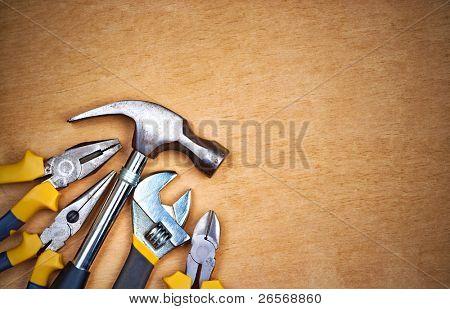 Conjunto de ferramentas sobre um painel de madeira com espaço para texto
