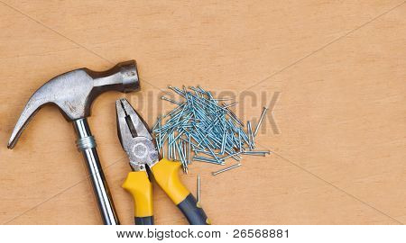 Set of manual tools and nails over a wooden board with space for text