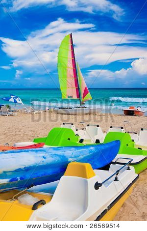 Colorful kayaks, water bikes and catamaran on the cuban beach of Varadero