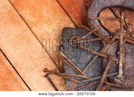 Old rusty saw and nails over a wooden boards background