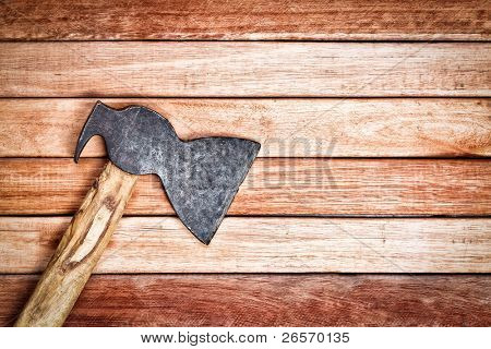 Ax over a wooden boards background