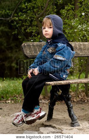 The offended boy sit on a bench in park