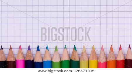 Close-up image of multicolor pencils on paper background