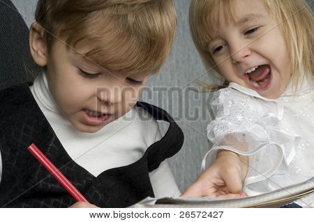 Beautiful little girl and boy is drawing with crayons on paper