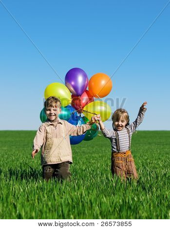 Happy sister and brother with balloons walking on spring field