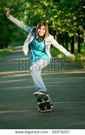 Beautiful teenage girl with skateboard in the green park