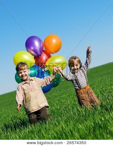 Los niños y niñas felices con globos caminando en el campo de primavera