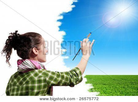 Menina bonita com pincel pinta o céu