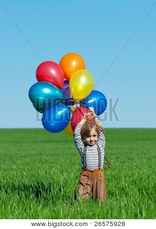 Happy girl with balloons walking on the spring field