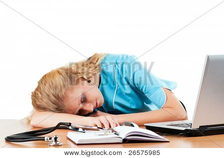 Beautiful young doctor sleep near laptop isolated on white background