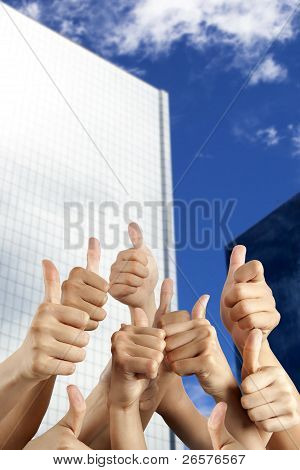 people's hand with thumbs up in front of modern building