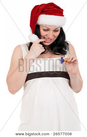 Portrait of a pregnant woman in santa hat with baby's dummy over white background. Third trimester.