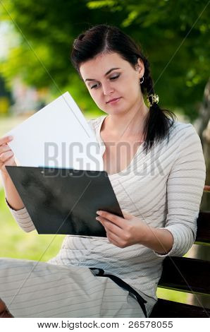 Portrait of smiling modern young business woman in park outdoors