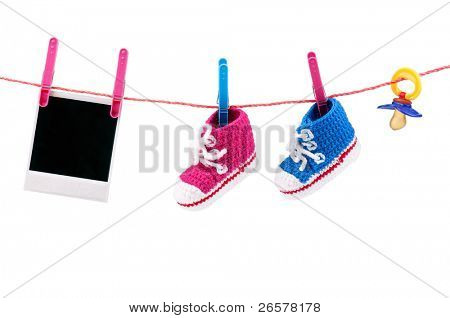 Baby bootees, photo and dummy on the clothesline on a white background