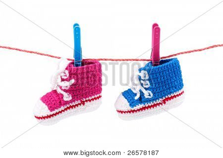 Baby bootees on the clothesline on a white background