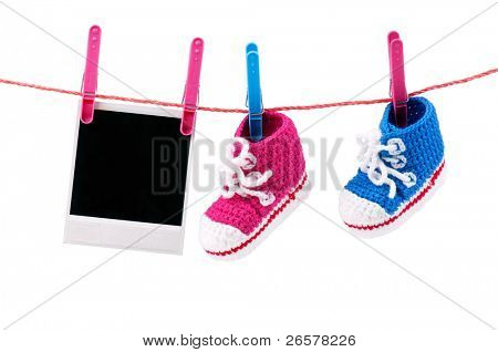 Baby bootees and photo hanging on the clothesline on a white background