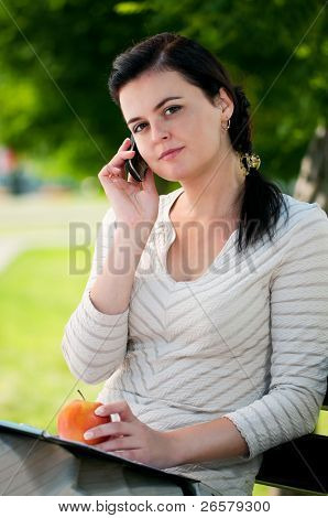Portrait of smiling modern young business woman with mobile cell phone in park outdoors