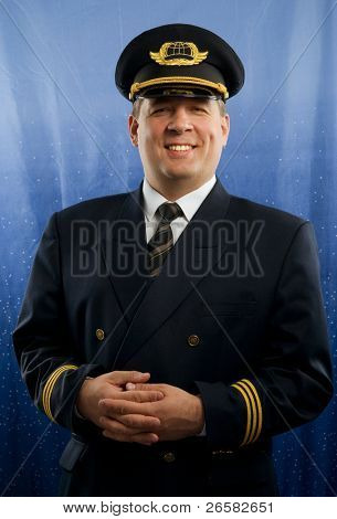 A smiling pilot in uniform on blue background.