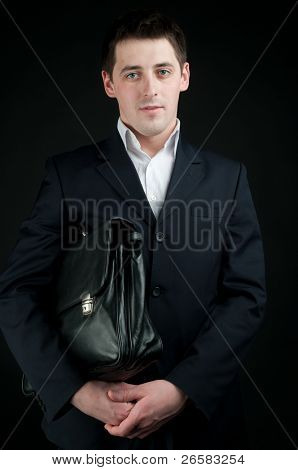 businessman with briefcase over black background