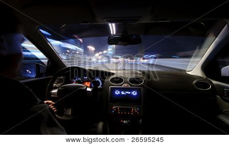 Night road. View from inside car. Natural light. Street and other cars is motion blurred.