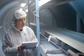 stock photo of factory-worker  - Quality inspector monitoring the process of crystal sugar production - JPG