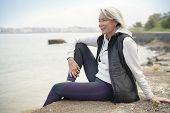 Beautiful elderly woman sitting by the ocean in sportswear                               poster