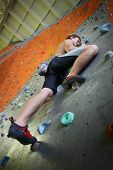 stock photo of climbing wall  - Young man climbing indoor wall - JPG