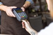 Cropped Shot Of Waiter Holding Payment Terminal While Customer Inserting Credit Card poster