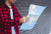 Young Man Looking In Open Map. Traveler Standing With Road Map In Hands. poster