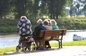 stock photo of senior-citizen  - Some seniors sitting on a bench having a good conversation - JPG