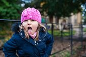 Cute Naughty Caucasian Girl Wearing Pink Hat Sticking Her Tongue Out poster