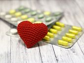 Medical Pills And Red Knitted Heart On Light Wooden Table, Selective Focus. Concept For Health Care, poster
