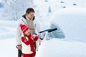 Father And Child Brushing Off Car In Winter. poster