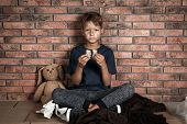 Poor Homeless Boy Holding Bread In Hands Near Brick Wall poster