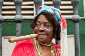 HAVANA-FEBRUARY 10:Wrinkled old lady with a huge cigar wears typical clothes and afrocuban religious
