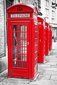 stock photo of phone-booth  - Row of iconic London red phone cabins with the rest of the picture in black and white - JPG